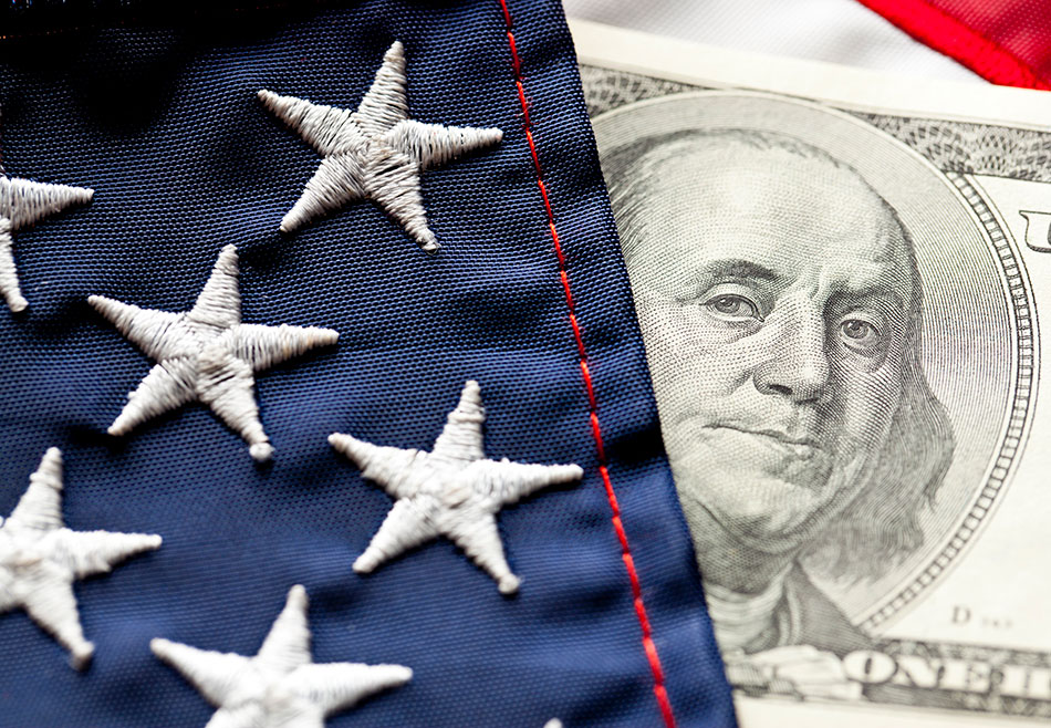 A closeup of part of an American flag next to a $100 dollar bill showing Benjamin Franklin's face.