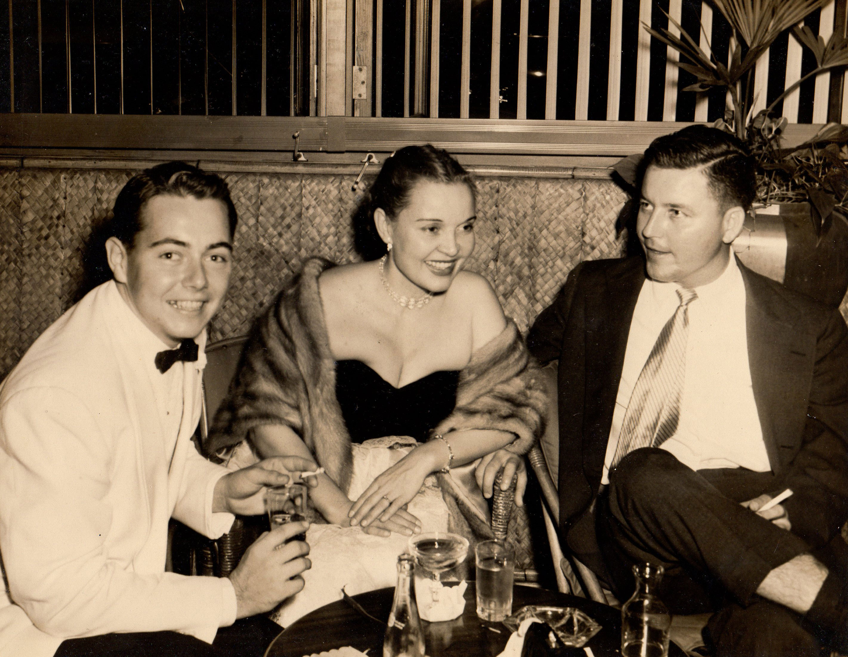 Picture from the 1950s of glamorous young professionals at a bar.