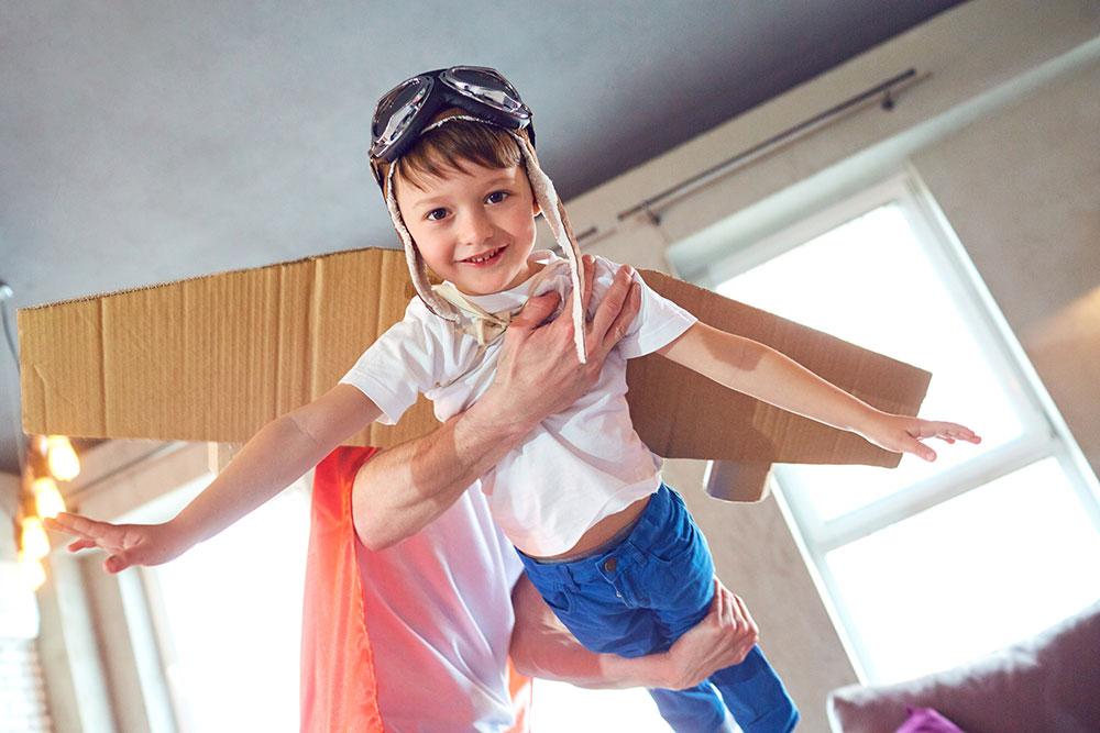 Child dressed as flying superhero
