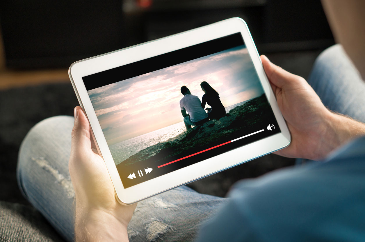 Hands holding tablet on which a video is playing