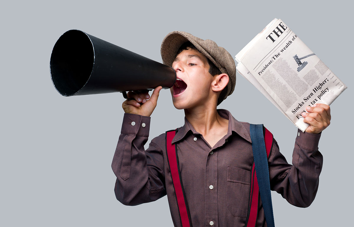 newspaper boy holding up a paper and speaking into a megaphone