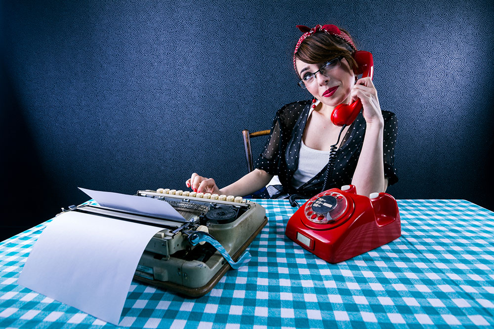 Woman talking on a rotary telephone sitting at table with typewriter