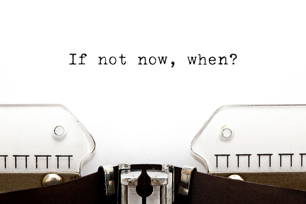 "The words ""If not now, when"" on a sheet of paper coming out of a typewriter."