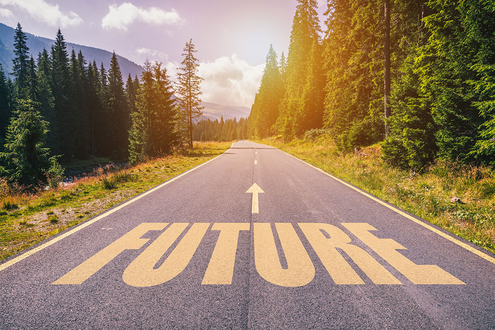 "Road through woods with the word ""Future"" on the pavement in yellow"